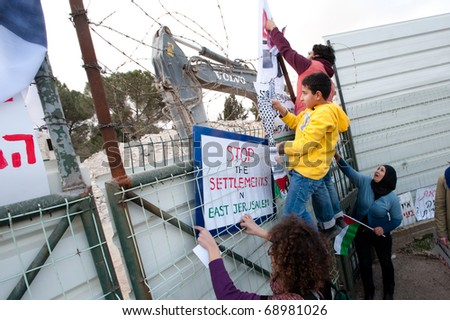 EAST JERUSALEM - JANUARY 14: Palestinian and Israeli activists climb the fence at a building demolition site while protesting the construction of Israeli settlements in East Jerusalem on Jan 14, 2011.