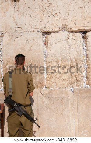 EAST JERUSALEM, OCCUPIED PALESTINIAN TERRITORIES - SEPTEMBER 4: An Israeli soldier with M16 assault rifle prays at the Western Wall in the Old City of Jerusalem on Sept 4, 2001.