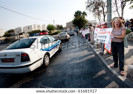EAST JERUSALEM - SEPTEMBER 24: An Israeli police car passes activists protesting Israeli settlements in the Arab East Jerusalem neighborhood of Sheikh Jarrah on Sept. 24, 2010 in East Jerusalem.