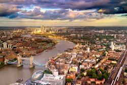 East London Skyline showing Tower Bridge,  Canary Wharf, City Hall and the Thames River. Taken during a cloudy sunset.