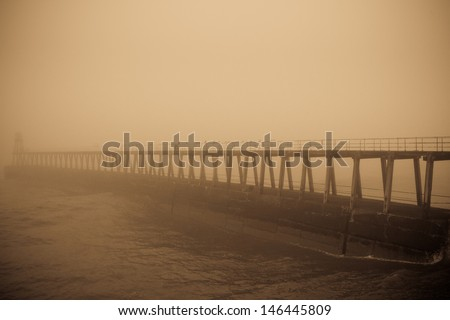 East pier, Whitby, partially obscured by thick fog.