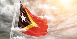 East Timor (Timor-Leste) national flag cloth fabric waving on beautiful grey sky.