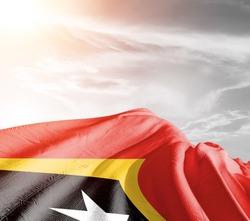 East Timor (Timor-Leste) national flag cloth fabric waving on beautiful sky background.