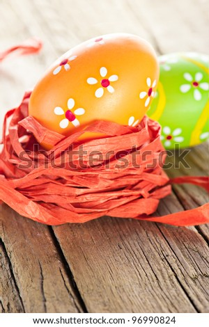 Easter background. Macro shot of painted eggs and ribbon decoration on old wooden texture