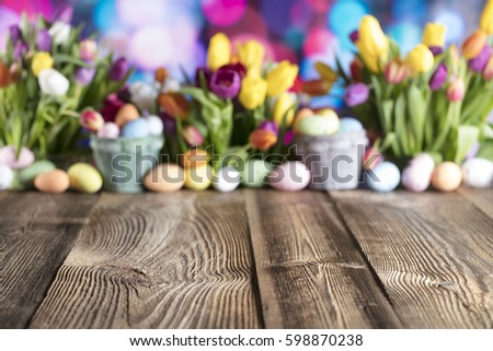 Easter background. Old wooden table, easter theme and beautiful colorful bokeh.