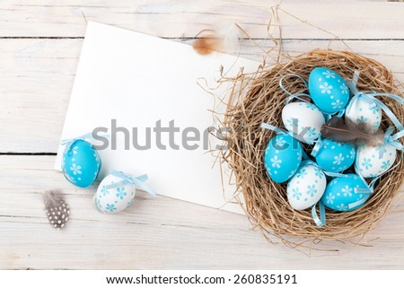 Easter background with blue and white eggs in nest and greeting card over white wood. Top view with copy space