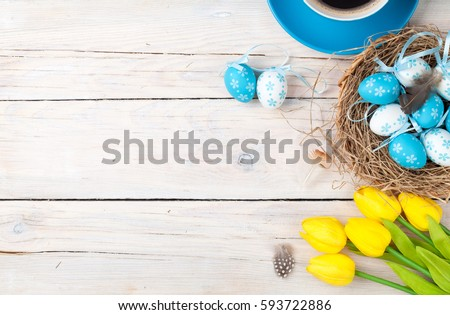 Easter background with blue and white eggs in nest, yellow tulips and coffee cup over white wood. Top view with copy space #593722886
