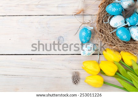 Easter background with colorful eggs and yellow tulips over white wood. Top view with copy space  #253011226