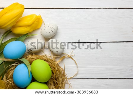 Easter background with colorful eggs in nest and yellow tulips over white wood. Top view with copy space