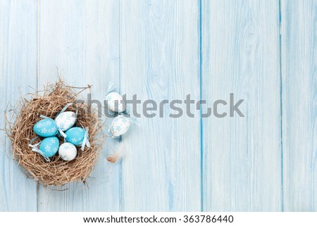 Easter background with eggs in nest over wood. Top view with copy space #363786440