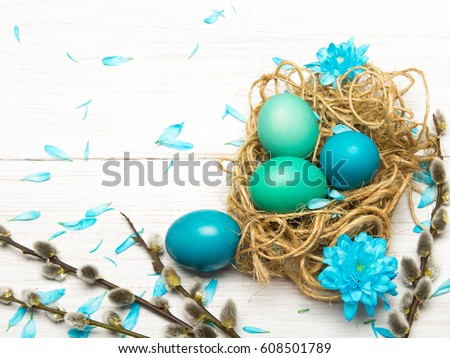 Easter background with eggs, nest and catkins on white wooden background, copy space #608501789