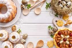 Easter background with  mazurek pastry, yeast cakes and quail eggs on rustic white wooden background, top view, copy space. Traditional easter