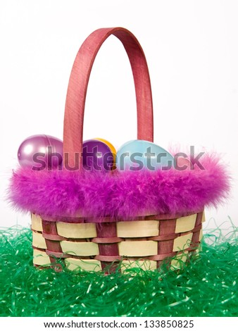 Easter basket with colorful eggs sitting on fake grass