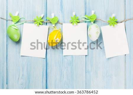 Easter blank photo frames and eggs over wood background