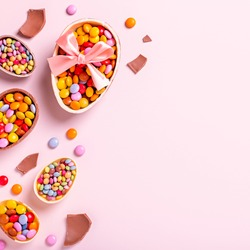 Easter border with chocolate eggs and colorful candy sweets on pastel pink, copy space. Traditional Easter treats flat lay, holiday background