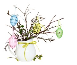 Easter bouquet of dry twigs and small spring green leaves with colorful glitter decorative eggsand ribbon bows in a white jug isolated on white background
