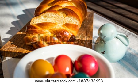Easter breakfast, yeast bread plaited, bunny and easter eggs, plait on a bread board, with colored eggs in a Porcelain bowl. plaited or braided, yeast bun. Stock foto ©