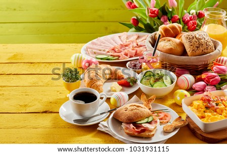 Easter buffet breakfast or brunch with assorted bread rolls, cheese, meat, scrambled egg, orange juice, coffee on a wooden table decorated with easter eggs and spring flowers with copy space