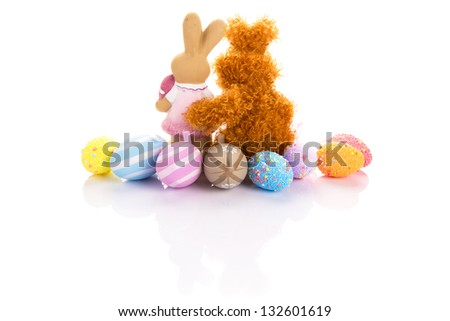 Easter bunnies in hug and eggs over white background