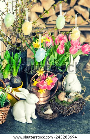 Easter bunny and eggs decoration. Spring flowers tulips, snowdrops and narcissus blooms. Retro style toned picture. Selective focus