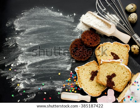 Easter bunny cake preparing in kitchen. Holiday food background with creative cake and baking ingredients on black background top view with copyspace