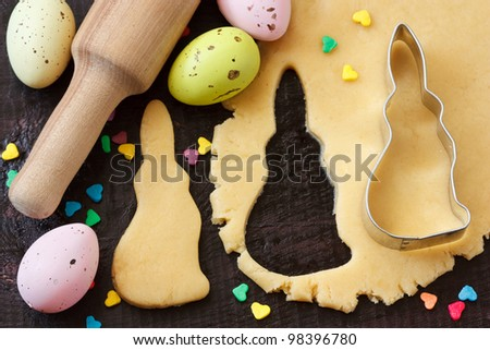 Easter bunny cookies, rolling pin and eggs on an old wooden table.