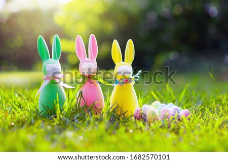 Easter bunny in face mask during coronavirus outbreak. Decoration and celebration during global virus pandemic. Easter egg hunt in flu epdemic.