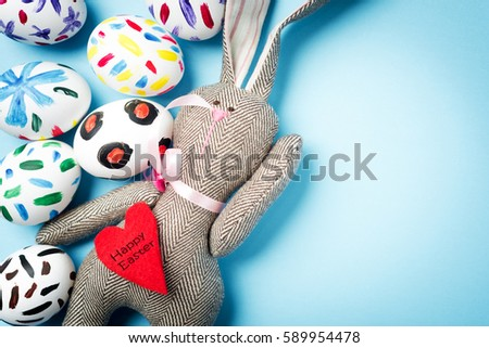 Easter bunny on a blue background with Easter eggs. Rabbit. Space for text. Black lettering on a heart .