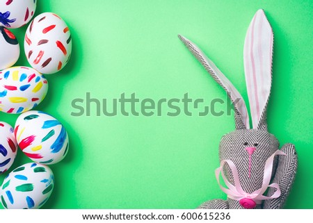 Easter bunny on a green background with Easter eggs. Rabbit. Space for text.