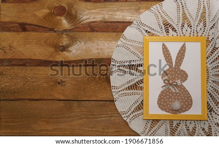 Easter bunny paper applique in yellow photo frame on an old wooden background. Top view. Happy Easter Day concept. Minimalizm. Easter card. Copyspace. Vintage.                                   Stok fotoğraf ©