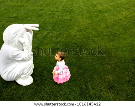 Easter bunny playing peep-bo with a little toddler while egg hunt #1016145412