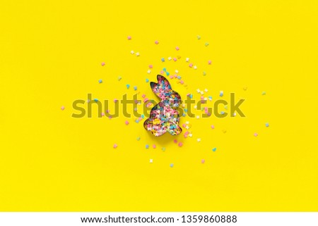 Easter Bunny shape form and scattering multicolored confectionery topping dressing on yellow paper. Concept Easter festive background. Copy space, Top view.