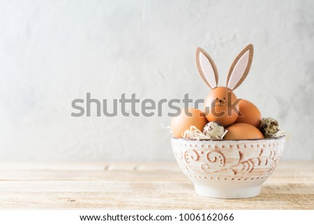 Easter bunny with eggs in bowl on grey background #1006162066
