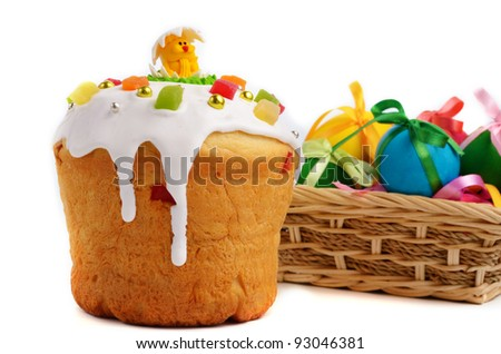 Easter cake and basket of painted eggs over white background