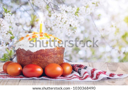 Easter cake and colored eggs on the background of cherry blossoms.
