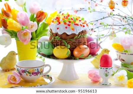 Easter cake and colorful eggs on festive Easter table - stock photo