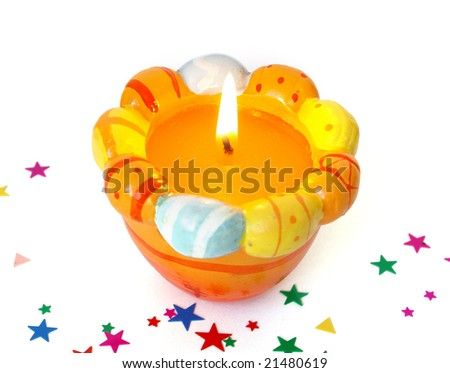 Easter candle and colorful confetti on white background
