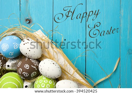 Easter card. Painted Easter eggs in a nest on a blue wooden background with copy space for congratulation
