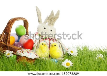 Easter card with eggs in basket and toy rabbits on green grass #187078289