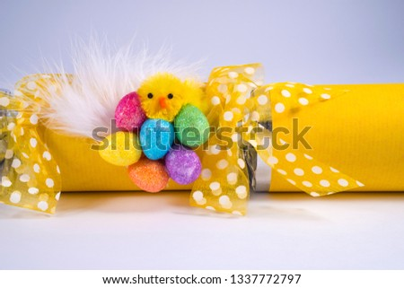 Easter Chick and eggs on an Easter Cracker also known as a Bon Bon. A traditional cracker consists of a cardboard tube wrapped in a brightly decorated twist of paper with a gift in the central chamber
