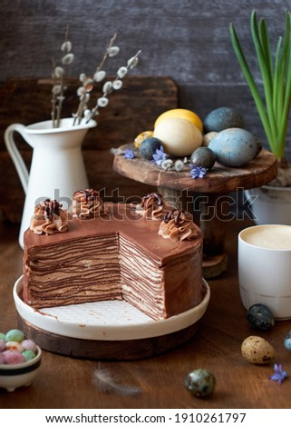 Easter chocolate crepe cake, decorated with cream, chocolate and nuts. Piece of cake. Wooden background. Easter colored eggs. Chocolate, coffee, purple flowers. Side view.