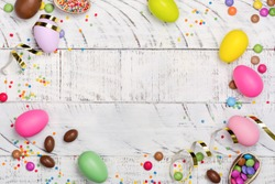 Easter chocolate egg and colorful candy sprinkles on white background. Copy space