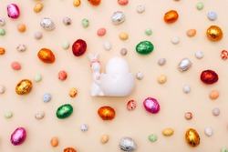 Easter chocolate mini eggs and candies scattered on a beige background with ceramic bunny stand for egg
