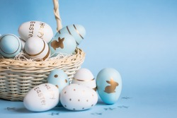 Easter colored eggs in a basket isolated on a trendy blue background. Minimal easter concept. Easter card with copy space for text.