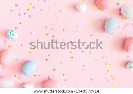 Easter composition. Easter eggs, confetti on pastel pink background. Flat lay, top view, copy space
