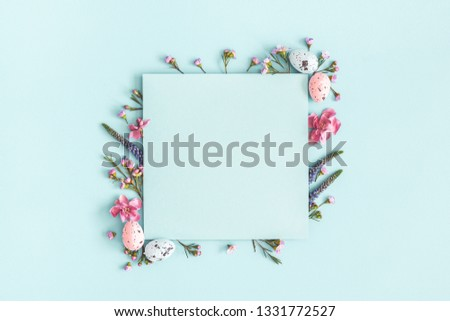 Easter composition. Easter eggs, flowers, paper blank on pastel blue background. Flat lay, top view, copy space.