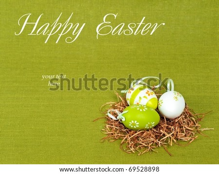Easter composition: nest with three colorful eggs on a green flax background (with space for text)