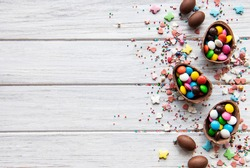 Easter composition with colorful and chocolate eggs on white wooden background, space for text. Top view, flat lay.