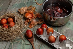 Easter concept. Easter egg coloring.  Easter eggs in an egg palette and nest on an old wooden table. Onion husk in the background