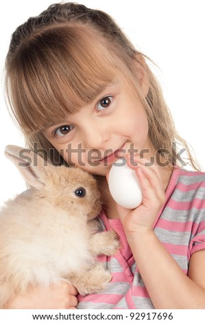 Easter concept image. Portrait of happy little girl with adorable rabbit and egg over white background.